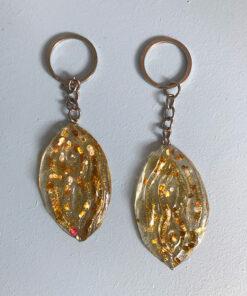 Gennemsigtig vulva nøglering med store og små stykker glitter.