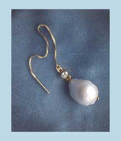 guld ørering med en lang kæde, en lille krystal og en stor smuk barok perle forneden.
