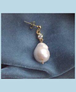 Guld ørering med lille krystal og barokperle nederst. En simpel ørering til et sofistikeret look