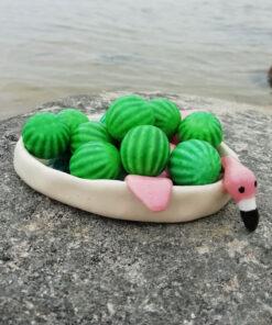 Flamingo i lille skål der ligger på maven med hovedet udover, dækket små vandmeloner