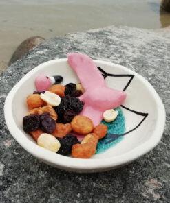 Flamingo i mellem skål fyldt med nødder og rosiner