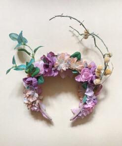 Blomsterkrans med lyserøde og ferskenfarvede blomster med sølv deltaljer. Kransen har forskellige udsikkere i form af grene