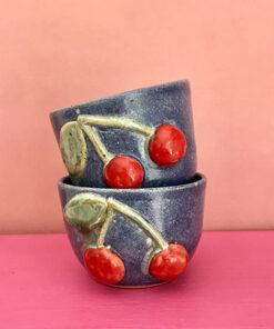 blå keramik kop med stort rødt kirsebær og grønne blade