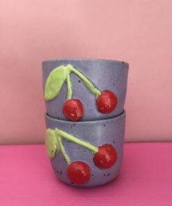lilla keramik kop med rødt kirsebær på fronten og limefarvede blade