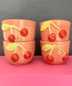 lyserøde kirsebær kopper med røde kirsebær og limefarvede blade