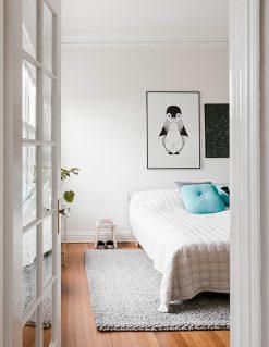 Grafiks plakat af baby pingvin med tynde sorte streger set som indretningsforslag i soveværelset