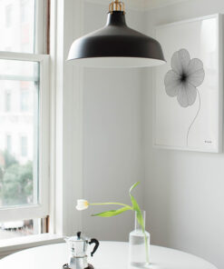grafisk illustration af firkløver lavet med tynde sorte streger ses på væg i køkkenet
