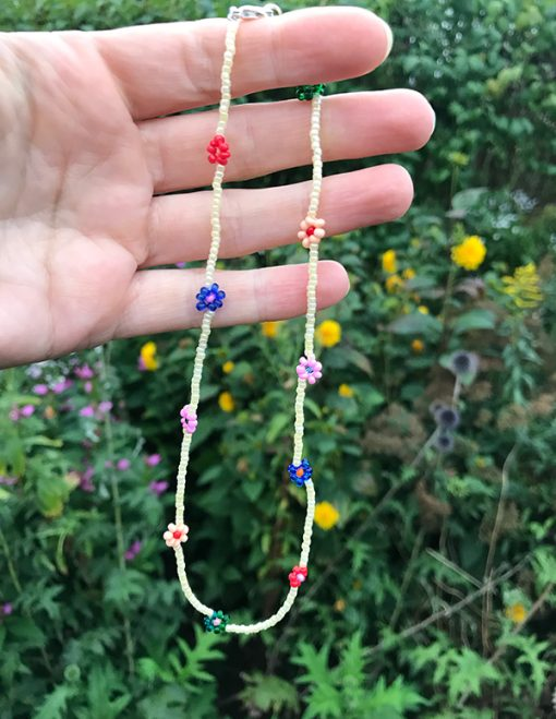 håndlavet perlekæde med blomster i forskellige farver med lysegule perler i mellem