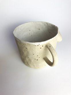 kaffekop med hank formet som en smuk kvindekrop, håndmodeleret i råt ler med hvidt glasur indvendigt