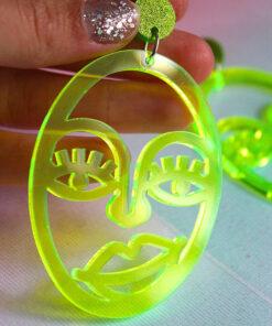 Plexiglas øreringe formet som et smukt ansigt i neon gul der lyser op i uv-lys