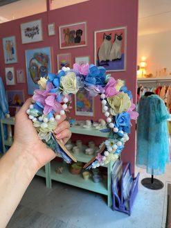 Pastelfarvet blomsterkrone med forskellige stofblomster der har fået nyt liv af Genfødt