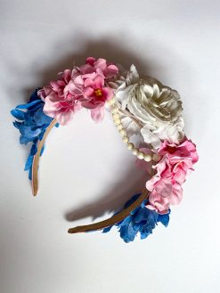 Lyserød og blå blomsterkrone med perlekæde hængende i midten fra Genfødt.