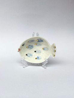 En lille skål fra Rikke Mangelsen formet som en fisk med trut mund, blå og guld prikker