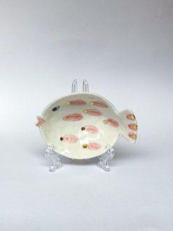 En lille skål fra Rikke Mangelsen formet som en fisk med trut mund,pink og guld prikker