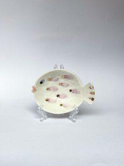 En lille skål fra Rikke Mangelsen formet som en fisk med trut mund, lyserøde og guld prikker