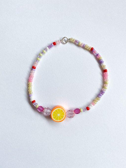 perlearmbånd fra Stines Perler med små perler i lyserøde nuancer og frugt perle